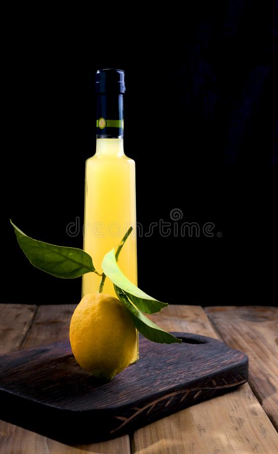 Lemoncello in a bottle on a black background, Traditional Italian liqueur from lemons. Alcohol yellow and fresh lemon with green royalty free stock photography