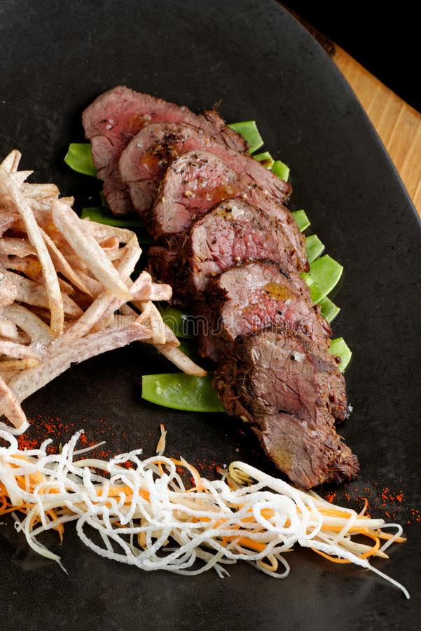 Lemongrass grilled beef steak with snow peas. And taro potatoes royalty free stock image