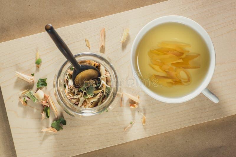 Lemongrasste, en kopp med drinken och en krus med torkade sidor royaltyfria bilder