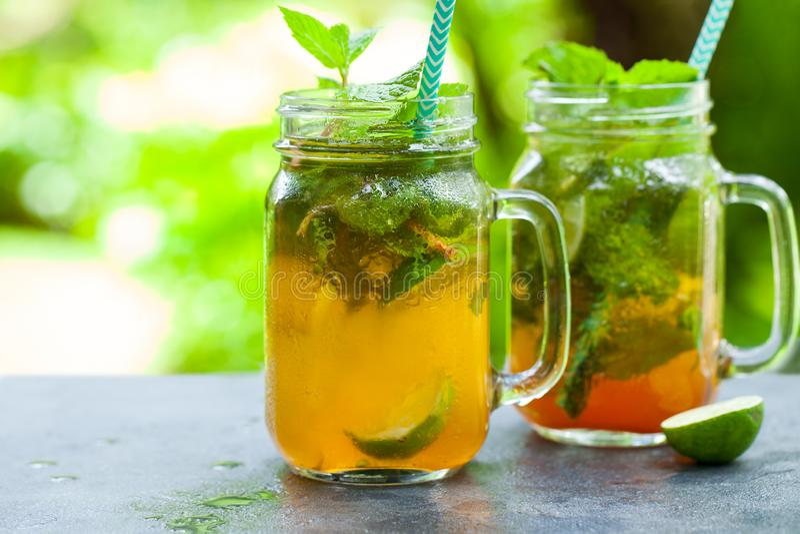 Lemoniada, lodowa herbata, natchnąca detox woda z wapno plasterkami w słoju Plenerowy tropikalny t?o kosmos kopii obrazy stock