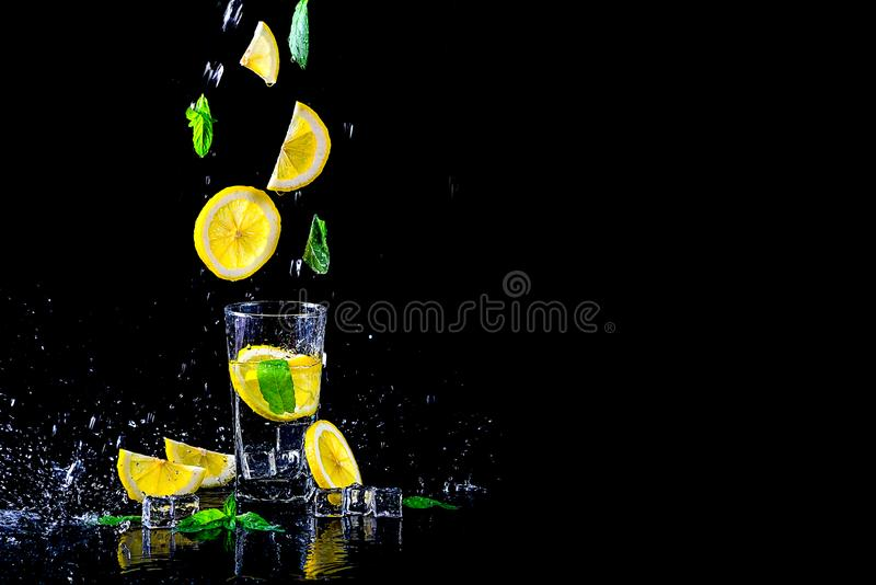 Lemoniada z latającą cytryną i mennicą odosobnionymi na czarnym tle, bezpłatna przestrzeń zdjęcie stock