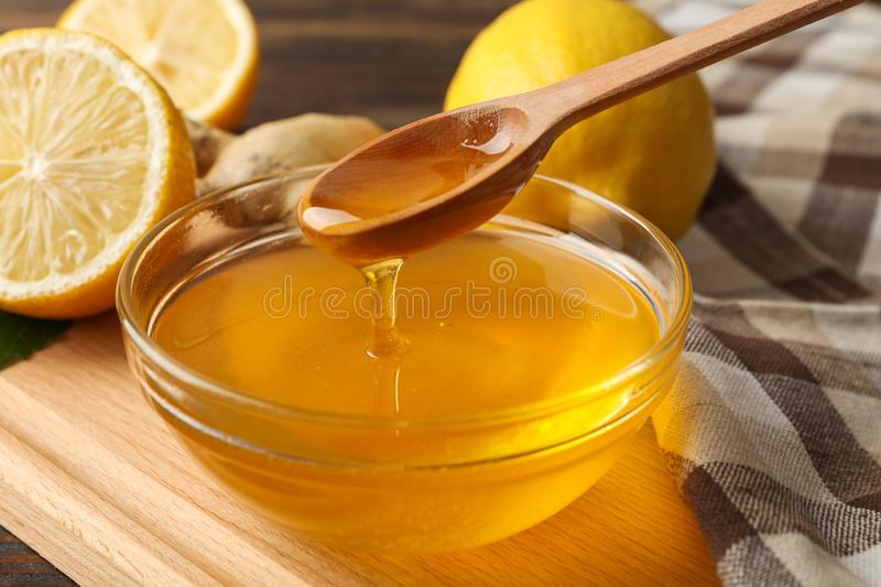 Lemons, bowl with honey and dipper on wooden background stock photos