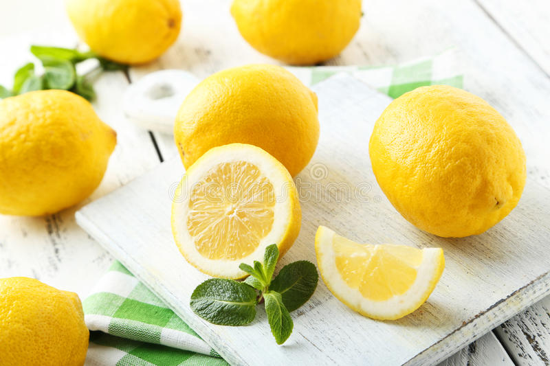 Lemons on cutting board. On white wooden background royalty free stock photography