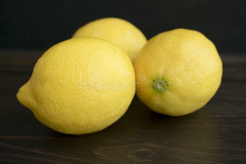 Lemons on a Dark Wood Background. Three yellow lemons grouped together on a dark wood background royalty free stock photos