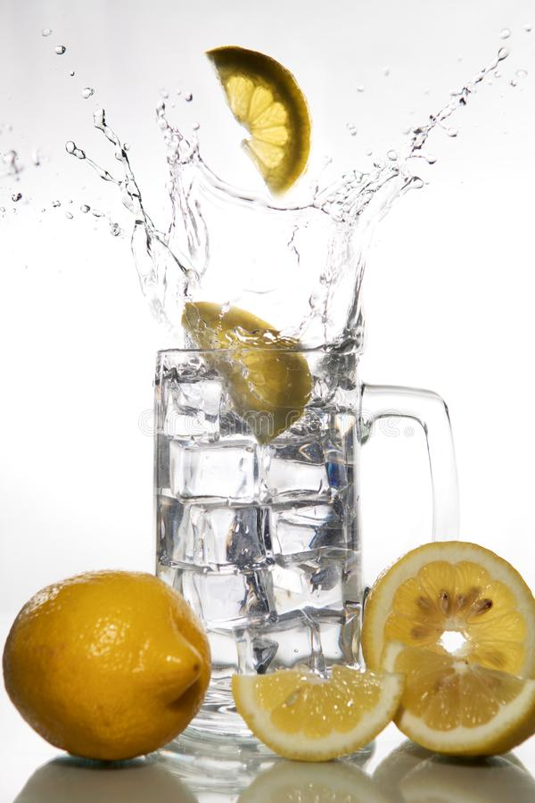 Lemons falling into a glass of ice water with splashes against isolated on white background. Refreshing Beverage stock photography
