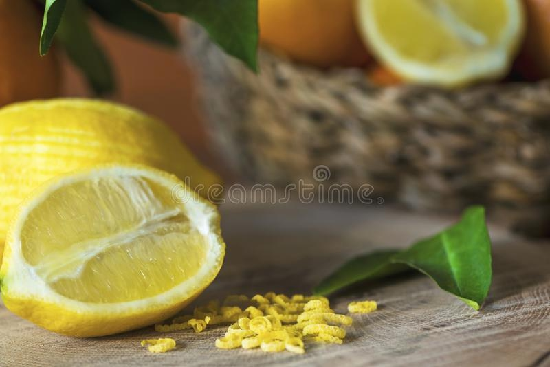 Lemons and lemon zests on a wooden log in front of a vegetable basket, still life photography, close up. royalty free stock images