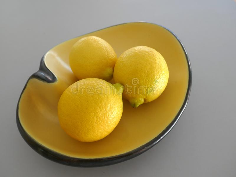 3 lemons in an old, ceramic bowl, yellow-black, kidney shape, 50s - 60s,, vintage, retro style,still life, close-up, isolated aga stock photo