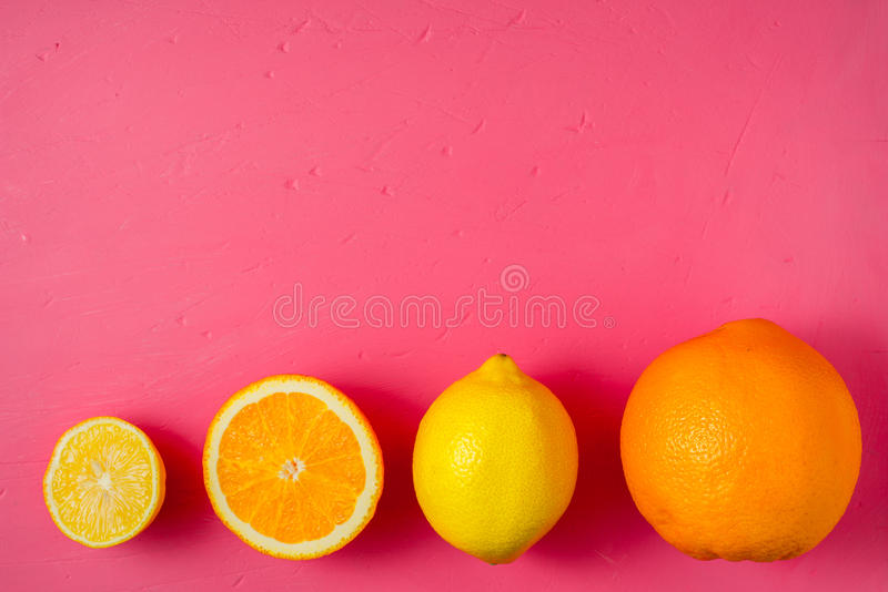 Lemons and oranges on the bright pink background stock photography