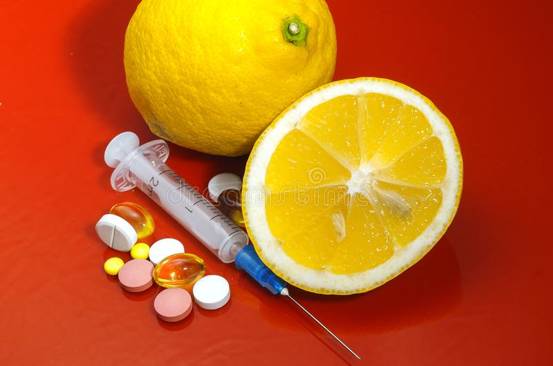 Lemons on a red background with syringes and pills. Medical preparations and vitamin C royalty free stock images