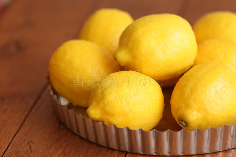 Lemons in a tart pan. Fresh bright yellow lemons sit in a pile inside a metal tart pan on a wooden table top stock image