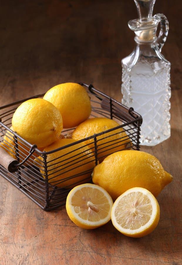 Lemons and vinegar. On wood background stock image