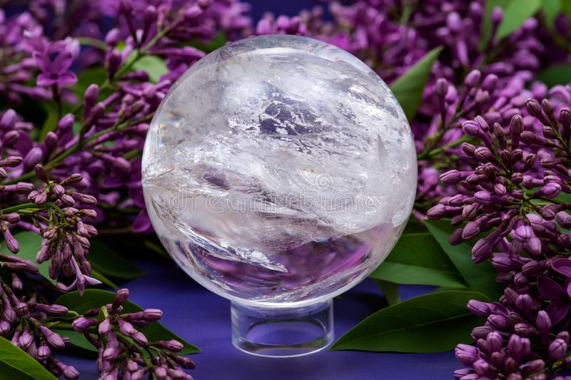 Lemurian Clear Quartz Sphere crystal magical orb surrounded by purple lilac flower. Lemurian Clear Quartz Sphere crystal magical orb surrounded by purple lilac stock photos