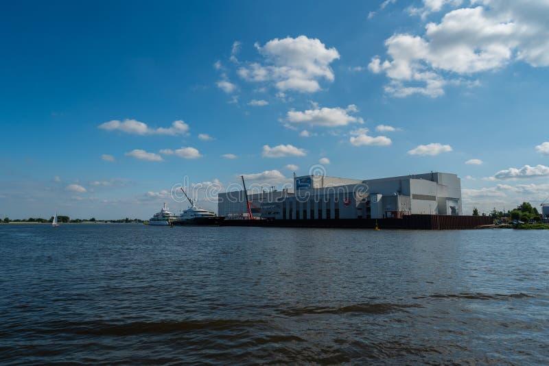 Lemwerder, Niedersachsen, Германия - 17-ое июля 2019 Изготовитель Abeking & Rasmussen яхты имеет свой главный завод здесь стоковое фото rf