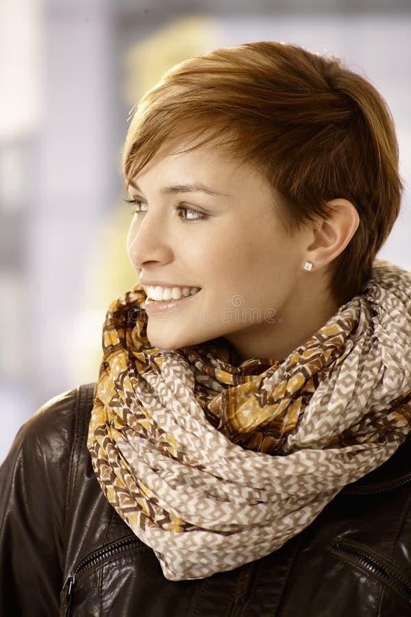 Lenço e casaco de cabedal vestindo da jovem mulher fotos de stock
