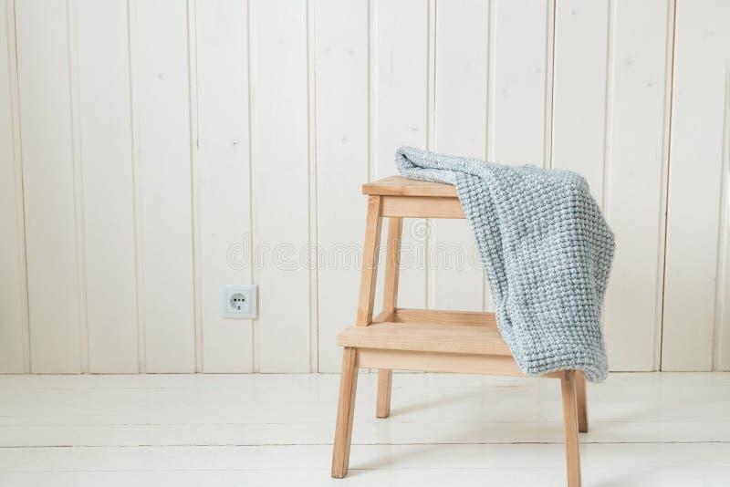 Lenço feito malha acolhedor em uma escada de madeira Estilo escandinavo foto de stock royalty free