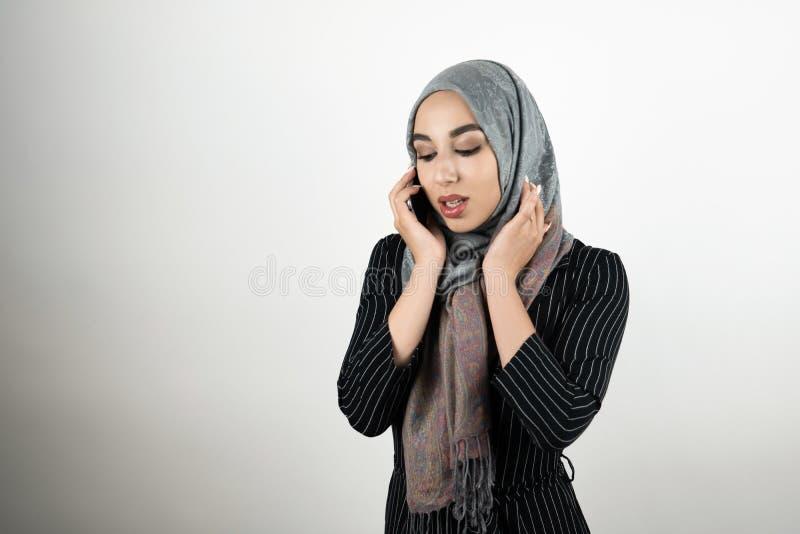 Lenço vestindo do hijab do turbante da mulher muçulmana bonita nova que tem a conversação no branco isolado smartphone fotografia de stock royalty free