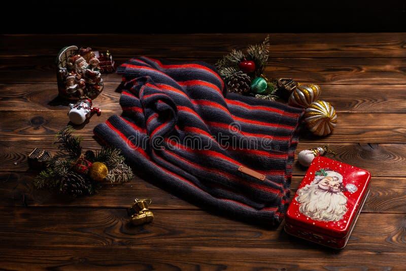 Len?o feito malha com as listras pretas, brancas e vermelhas, as decora??es do Natal e uma caixa do metal com uma imagem de Santa fotografia de stock royalty free