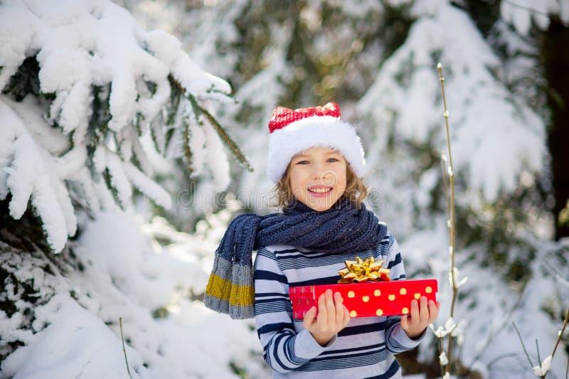 Lendemain de Noël Le garçon dans le chapeau du ` s de Santa et une écharpe juge une boîte lumineuse avec un cadeau disponible photos stock