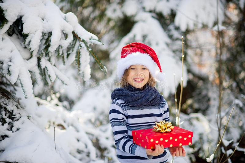 Lendemain de Noël Le garçon dans le chapeau du ` s de Santa et une écharpe juge une boîte lumineuse avec un cadeau disponible image libre de droits