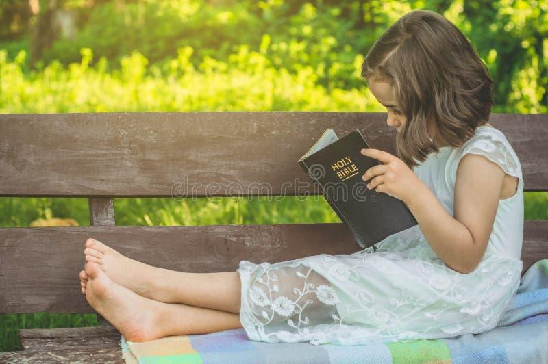 Lendo a Bíblia Sagrada no ar livre A menina cristã guarda a Bíblia em suas mãos que sentam-se em um banco foto de stock royalty free