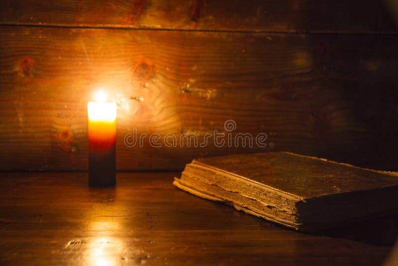 Lendo a cena em épocas antigas: um livro velho que inclina-se na tabela de madeira arruinada iluminada por uma vela em um fundo d imagem de stock royalty free