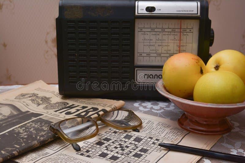 Lendo jornais soviéticos velhos, rádio do vintage fotografia de stock