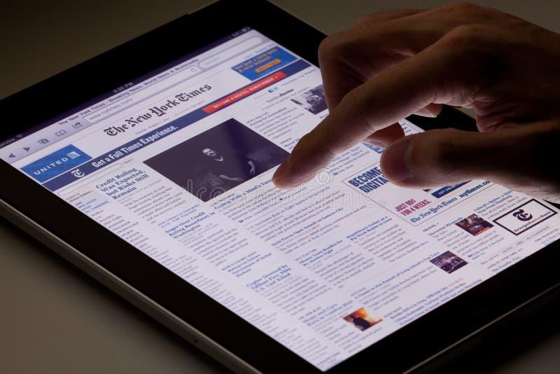 Lendo o jornal em linha no ipad imagens de stock royalty free