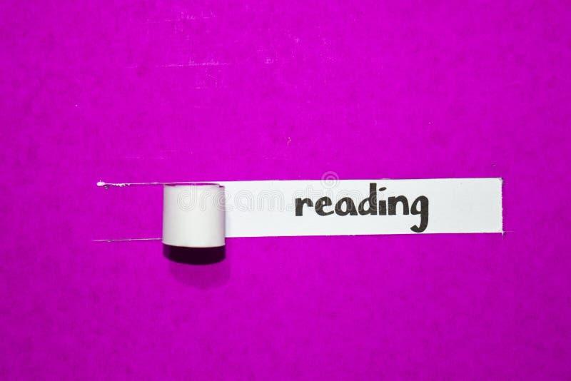 Lendo o texto, o conceito da inspiração, da motivação e do negócio no papel rasgado roxo fotografia de stock