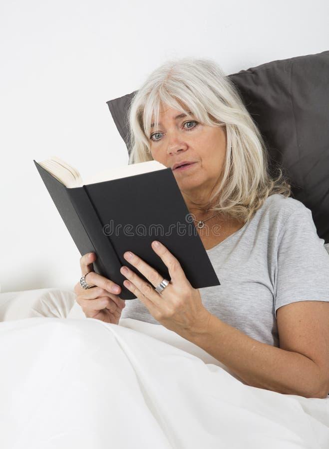 Lendo um livro do onicofagia imagens de stock