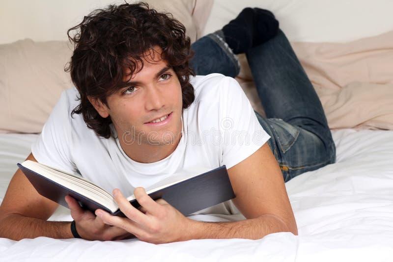 Lendo um livro na cama fotos de stock