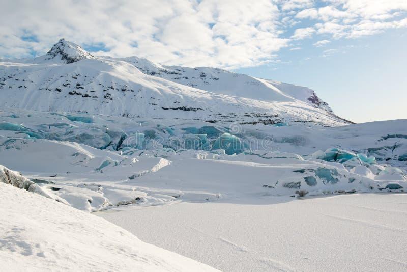 Lengua en invierno, icebergs azules del glaciar de Svinafellsjokull cubiertos por la nieve, Islandia fotografía de archivo