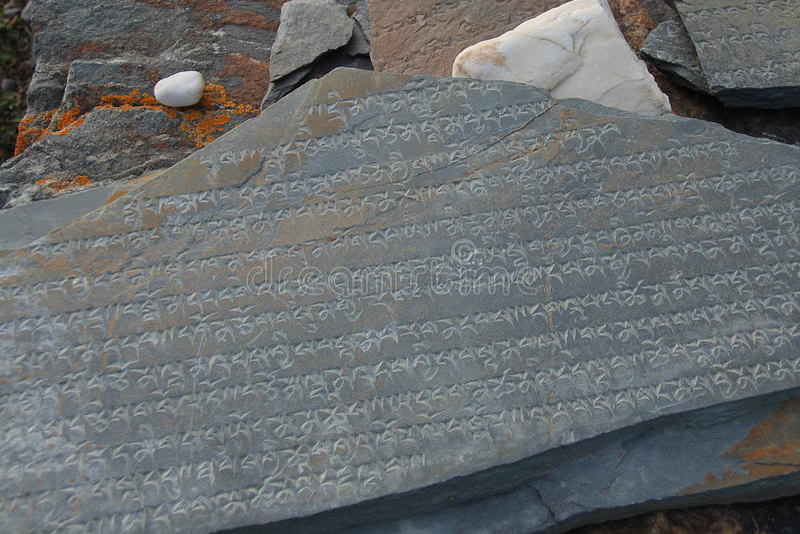 Lengua tibetana tallada en la piedra de Marnyi fotos de archivo