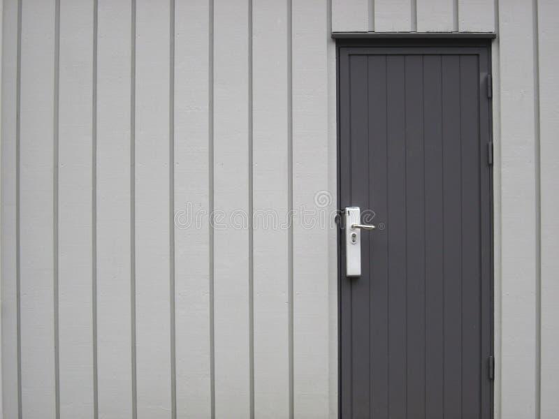 Lengua y madera del surco que artesona la pared y la puerta grises imagen de archivo