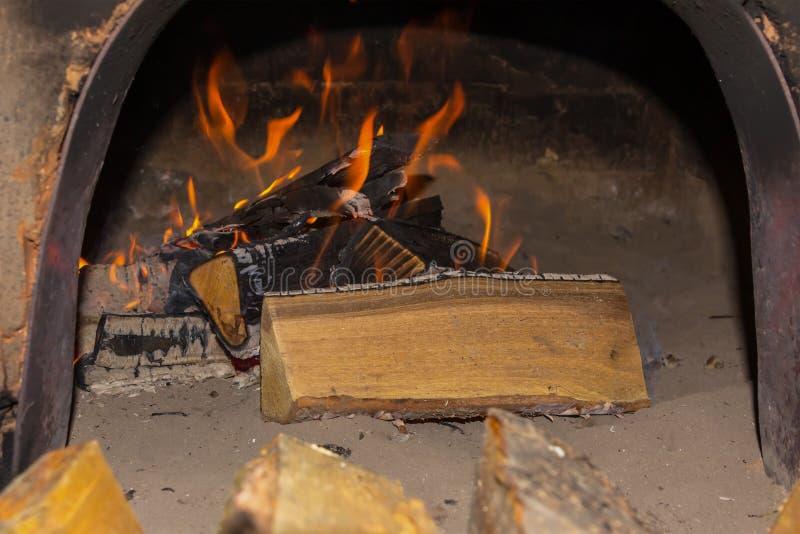 Lenguas anaranjadas del fuego de la chimenea de la llama brillante ardiente de los registros en la seguridad del fondo de la aren imágenes de archivo libres de regalías
