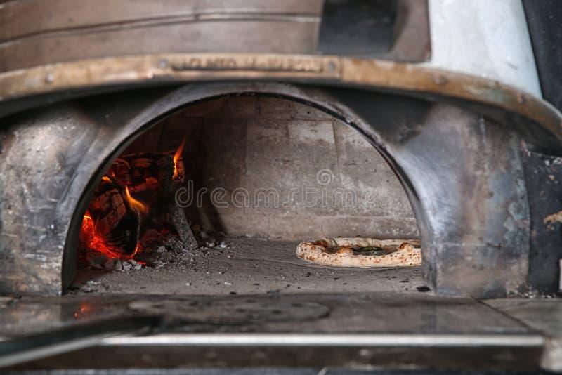 Lenha de queimadura e pizza saboroso no forno na cozinha imagem de stock royalty free