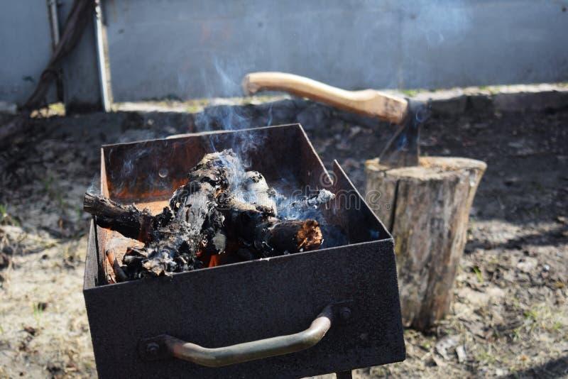 Lenha de queimadura no soldador velho com um machado no coto no fundo imagem de stock royalty free