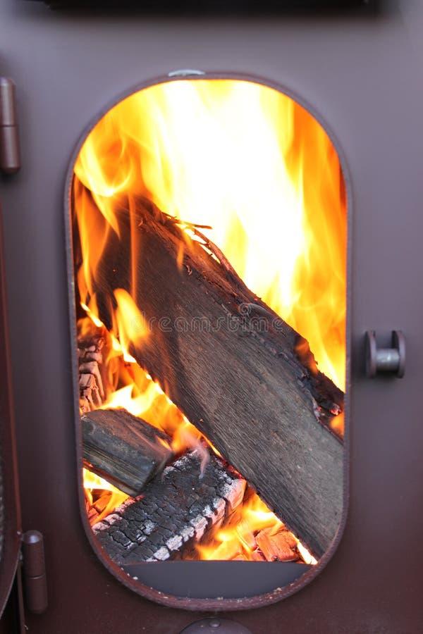 A lenha está queimando-se em uma fogo-câmara de um fogão com uma porta aberta imagens de stock royalty free