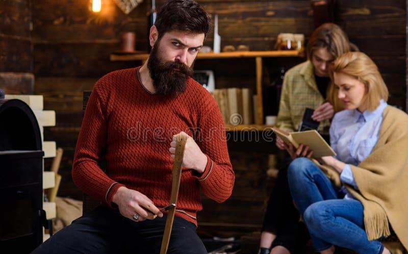 Lenhador com olhar restrito e a barba espessa longa que afiam a lâmina ou a faca, conceito do perigo Homem farpado no equipamento imagens de stock