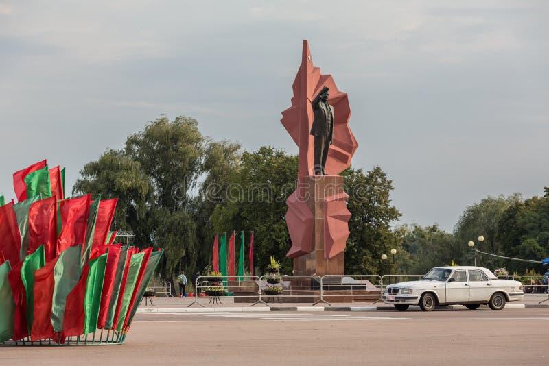 Lenin staty på den Lenin fyrkanten med flaggor i medborgarefärger och den sovjetiska retro bilen i Mozyr, sydliga Vitryssland arkivbild