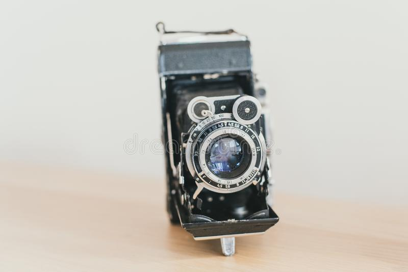 lens accordion on an old camera. Old vintage camera on a wooden light background royalty free stock image