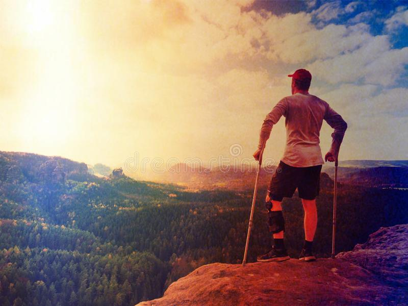 Hiker in grey t-shirt, medicine crutch and leg fixed in immobilize achieved mountain peak. Man has fixed broken leg in immobiliz stock images