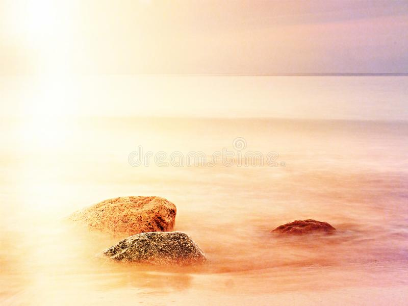 Long exposure of sea and big boulders sticking up from water within twilight time. Lens defect. Long exposure of sea and big boulders sticking up from water stock images