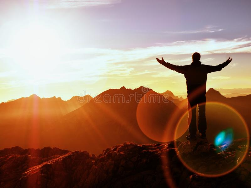 Lens flare. Happy hiker at peak of mountain with raised arms royalty free stock image