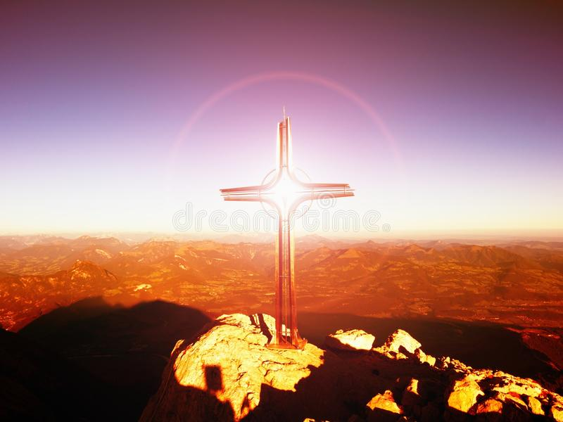 Lens flare light, strong effect. Cross on peak. Iron crucifix at mountain top in Alp royalty free stock images