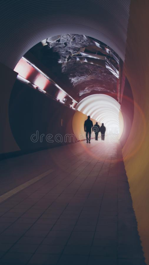 Free Lens-flared Silhouettes Of People In A Circular Tunnel For Pedestrians And Cyclists. Royalty Free Stock Images - 104747119