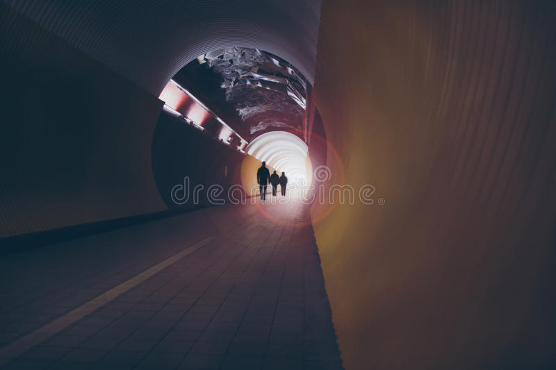 Lens-flared silhouettes of people in a circular tunnel for pedestrians and cyclists. Silhouettes of three people in a round tunnel for pedestrians and cyclists royalty free stock images