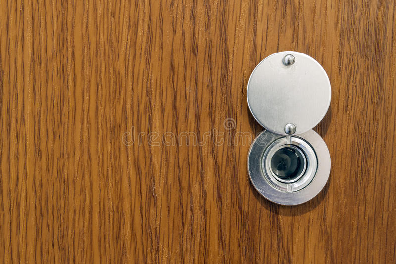 Lens peephole on new wooden texture front door.  stock images
