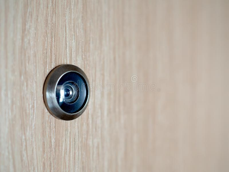 Lens peephole on wooden door. Close-up lens peephole on wooden door with copy space stock image