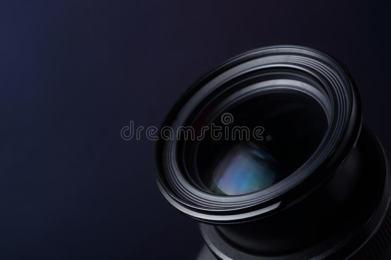 Lens of professional camera on dark blue background. Space for text. Lens of professional camera on dark blue background, closeup. Space for text royalty free stock images