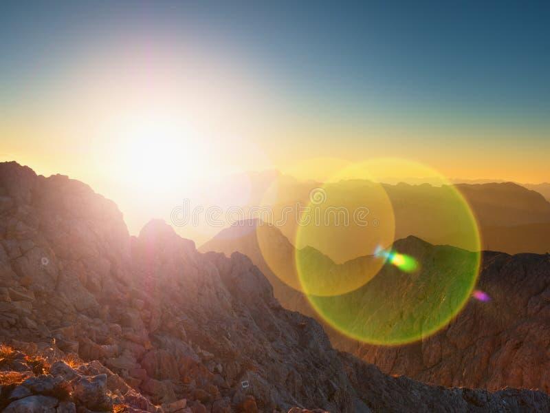 Lens signalljusljus, stark effekt Morgonsikt över den Apine klippan och dalen Gryningsol på horisonten arkivbilder